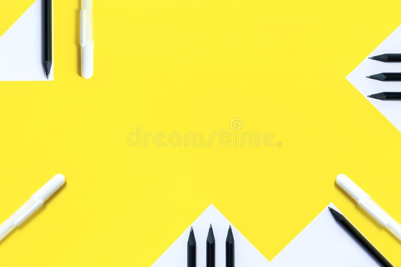 White paper, black pencils and white pens are randomly arranged on a yellow background. The concept is back to school. White paper, black pencils and white pens royalty free stock photography