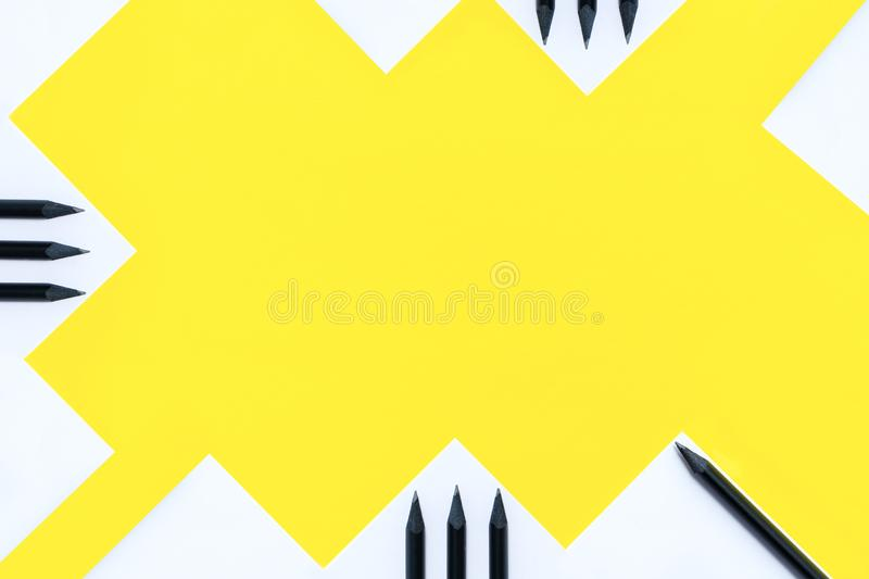 White paper, black pencils and white pens are randomly arranged on a yellow background. The concept is back to school. White paper, black pencils and white pens royalty free stock images