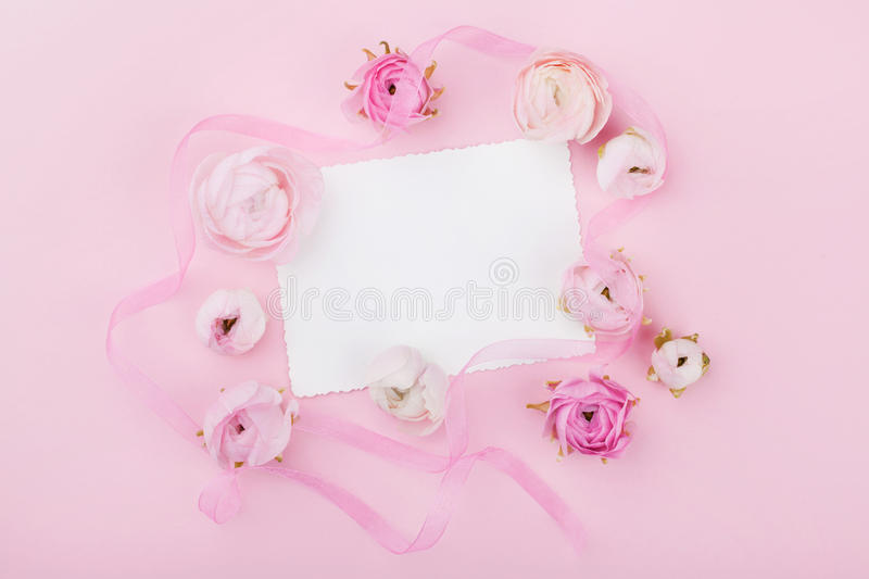 White paper blank and spring flower on pink desk from above for wedding mockup or greeting card on womans day. Floral frame. royalty free stock images