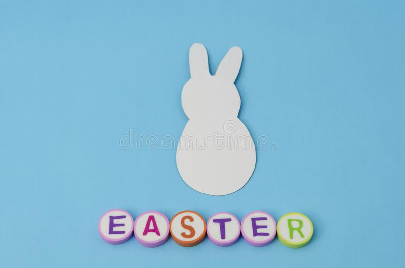 White paper bunny. Decoration for easter day. White paper bunny and easter made form colorful letters on blue background. Decoration for Easter Day royalty free stock photography