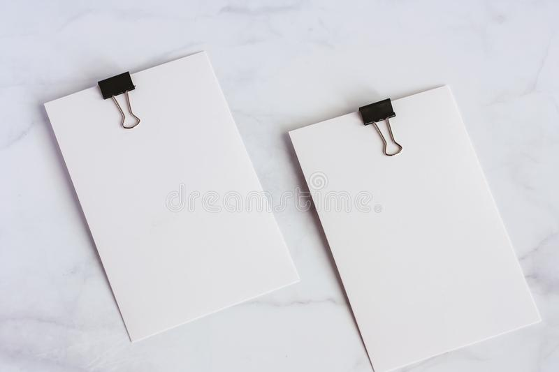 White paper card with binder clip on white marble background. For office and school supplies concept royalty free stock photography