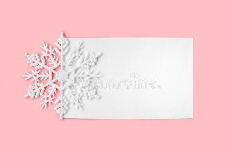 White paper card decorated with snowflake on pink background. New Year, Christmas and winter concept. Flat lay, top view, free copy space stock image