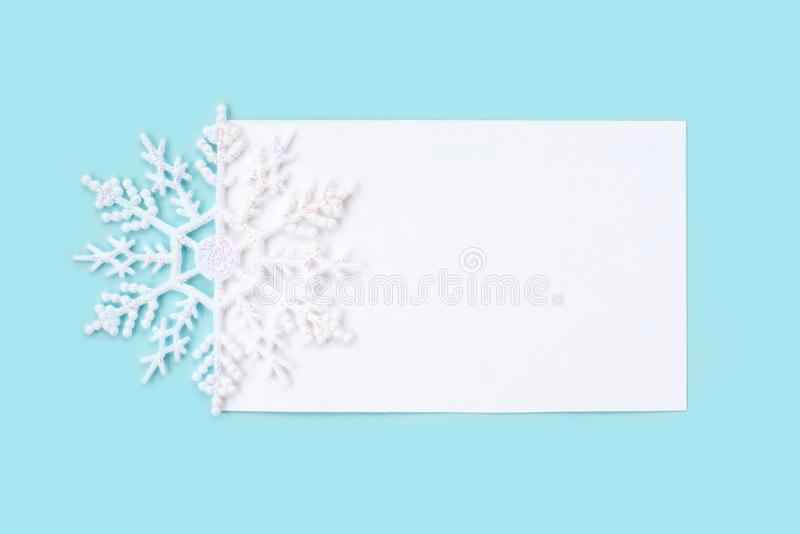 White paper card decorated with snowflakes on light blue background. stock photo