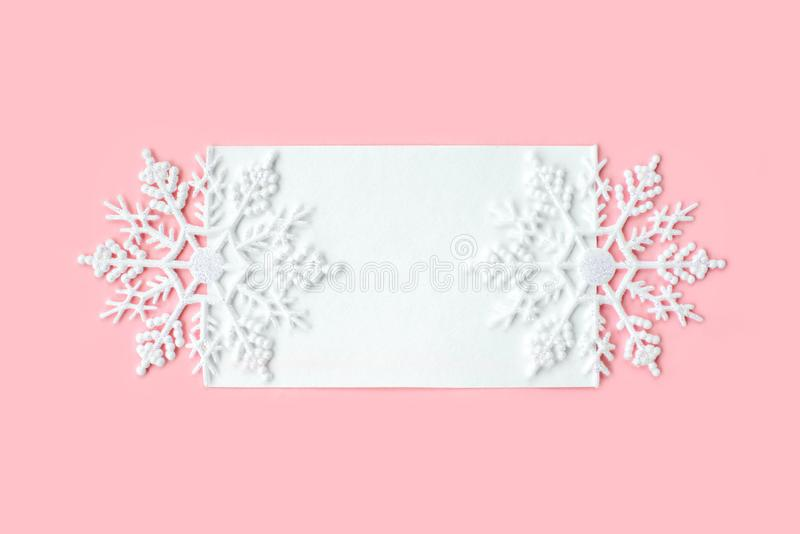 White paper card decorated with snowflakes on pink background. New Year, Christmas and winter concept. Flat lay, top view, free. White paper card decorated with stock images