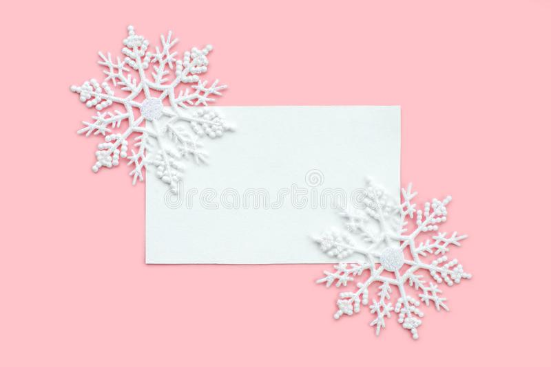White paper card decorated with snowflakes on pink background. New Year, Christmas and winter concept. Flat lay, top view, free. White paper card decorated with royalty free stock photos