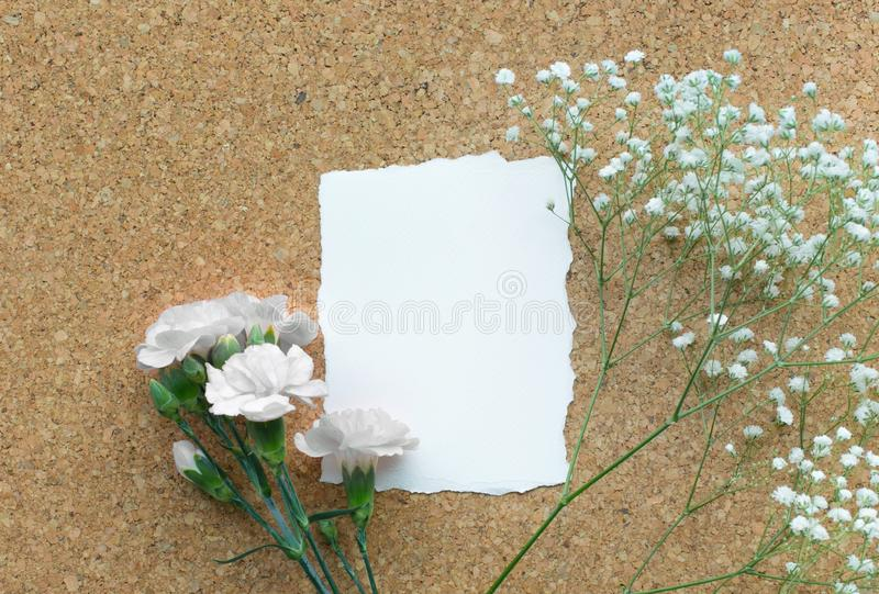 White paper card with flower on wooden corkboard royalty free stock photography