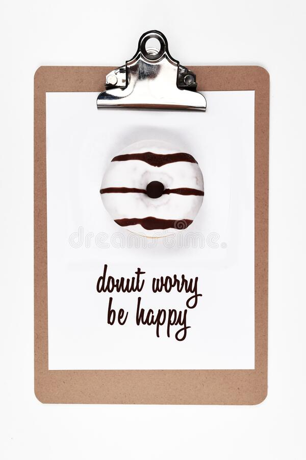 White paper on clipboard with real donut on it and wordplay text saying `Donut worry be happy`. On white background stock photos