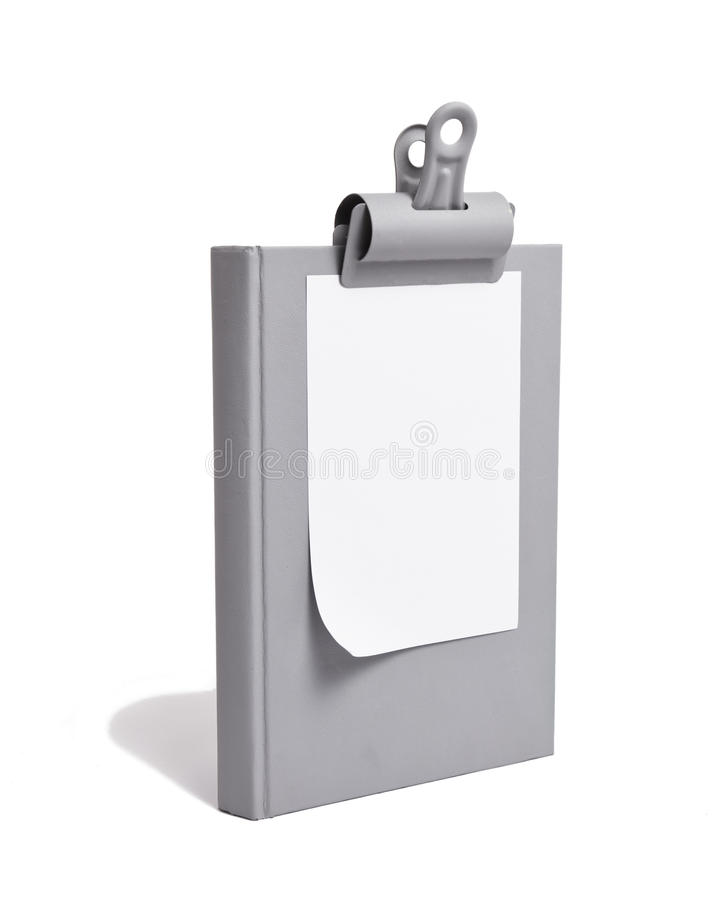 White Paper Clipped to Grey Book stock image