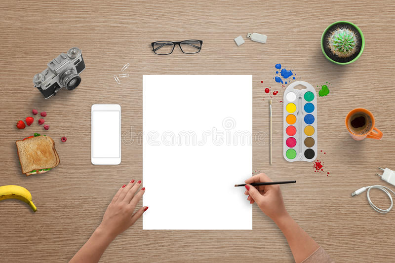 White paper for color brush art, font, logo presentation. Top view of table with mobile phone, glasses, plant, camera, sandwich, coffee beside royalty free stock photo