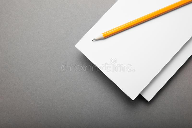 White paper flyer with pencil on a gray background.  stock photo