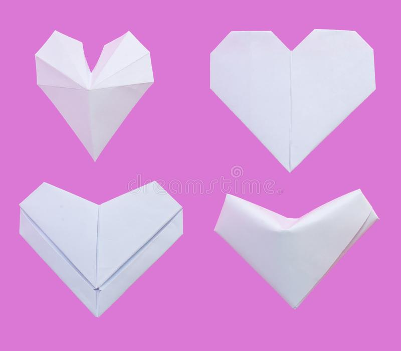 White paper folded into various heart shapes isolated on pink background. stock images