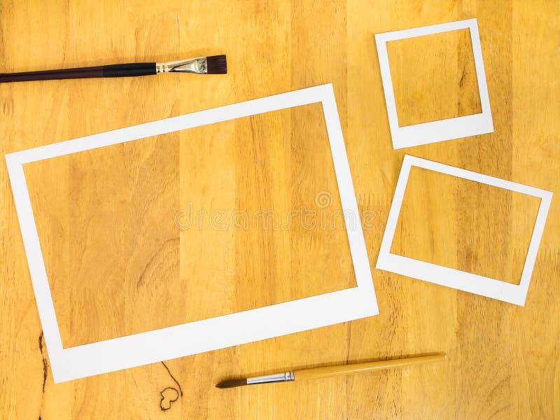 White paper frame with paintbrush on wood background. stock photo