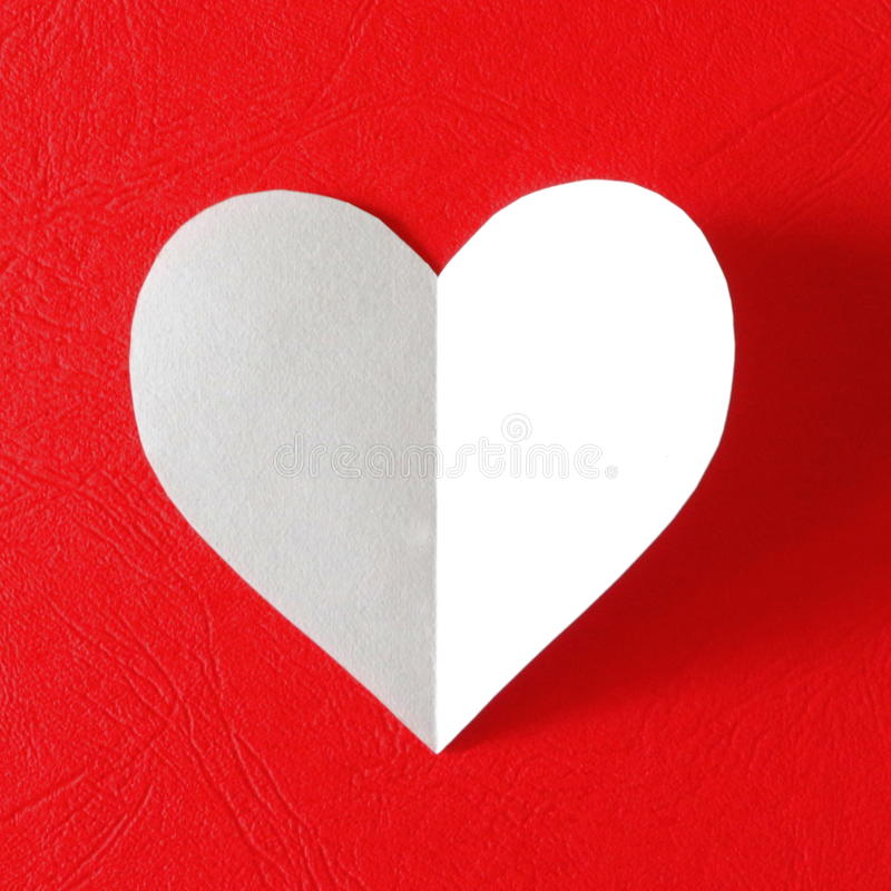 White paper heart. A white paper heart is placed on a red paper background with a shadow casted on the other side, symbolizing the mystery of love and royalty free stock photography