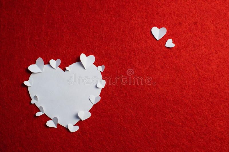 White paper heart it over the red background. Saint Valentine`s day royalty free stock photography
