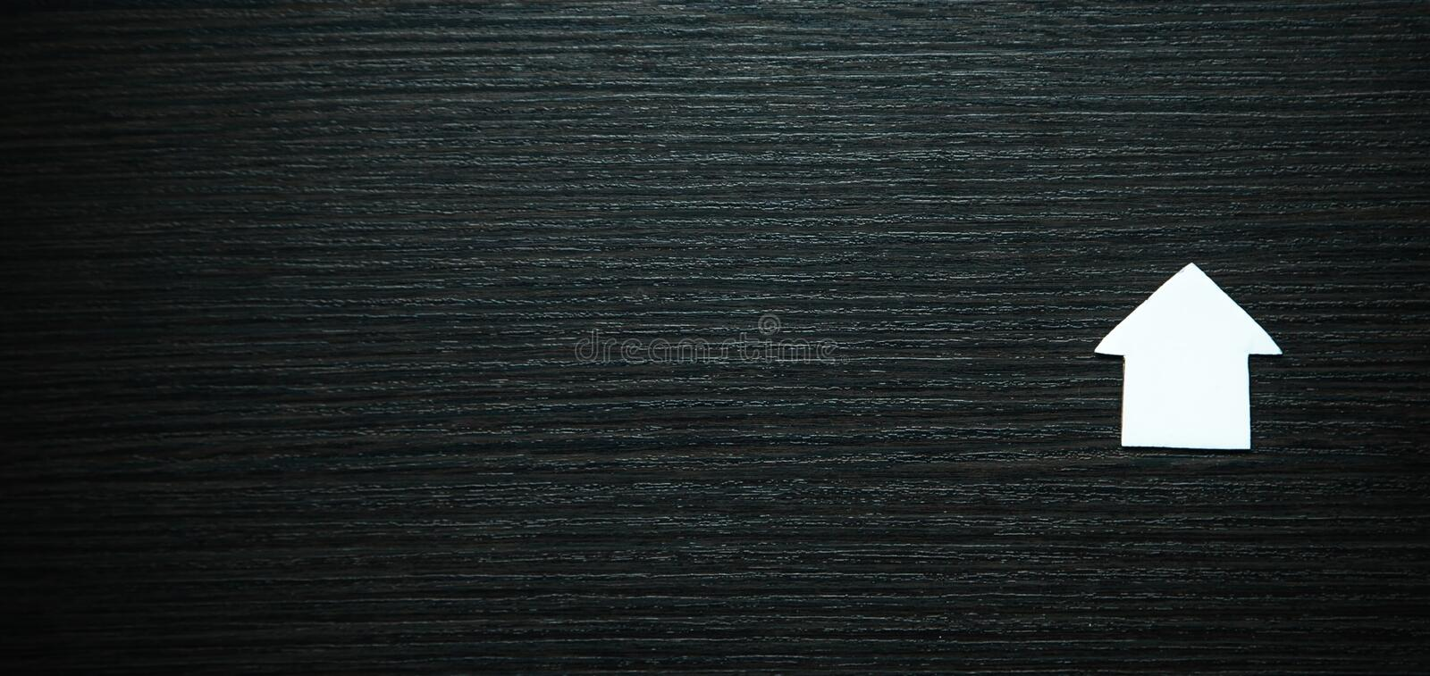 White paper house on black wood background. Real estate concept stock photo
