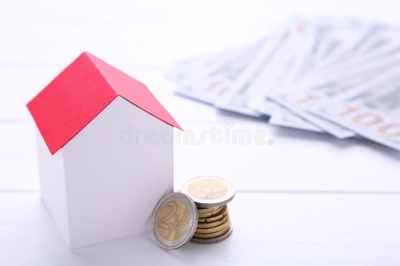 Blue paper house with coins isolated on white background. Blue paper house with coins on a white background royalty free stock photos