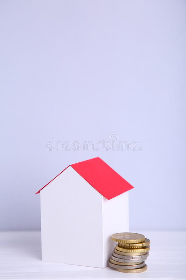 Blue paper house with coins isolated on white background. Blue paper house with coins on a white background stock photo
