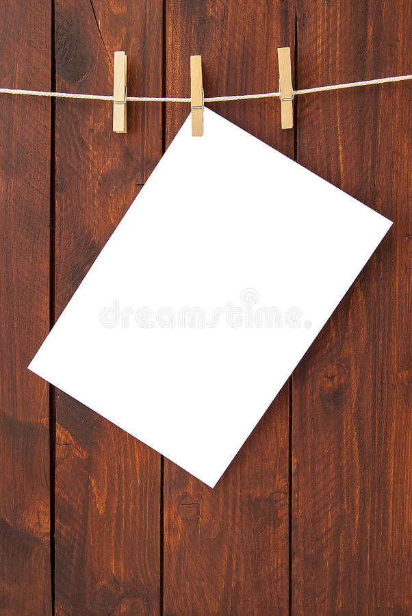 White paper hung on laundry line. With brown wooden board on the background stock photo