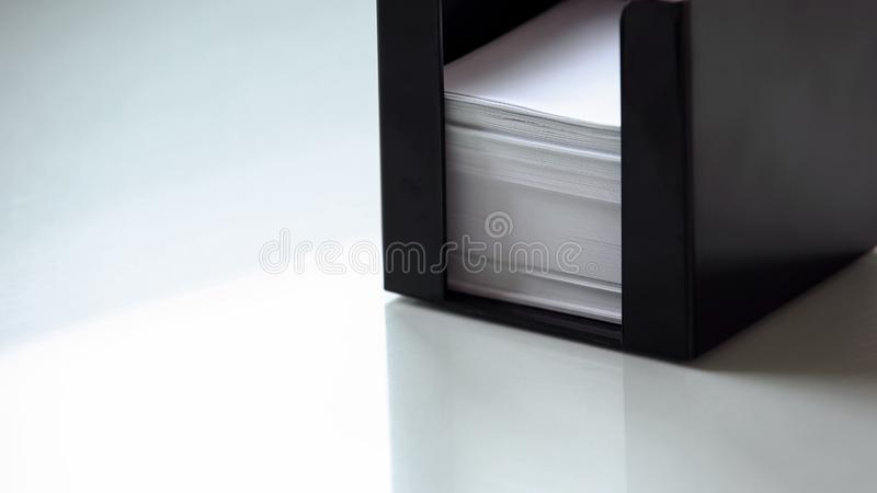 White paper in note holder on table, office supply organizing, work stationery stock photography