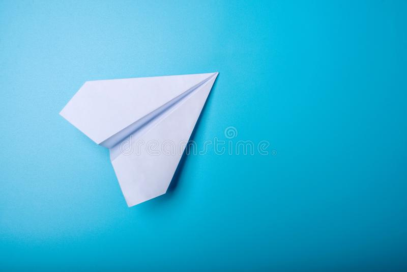 White paper origami airplane lies on pastel blue background. Top view royalty free stock photo