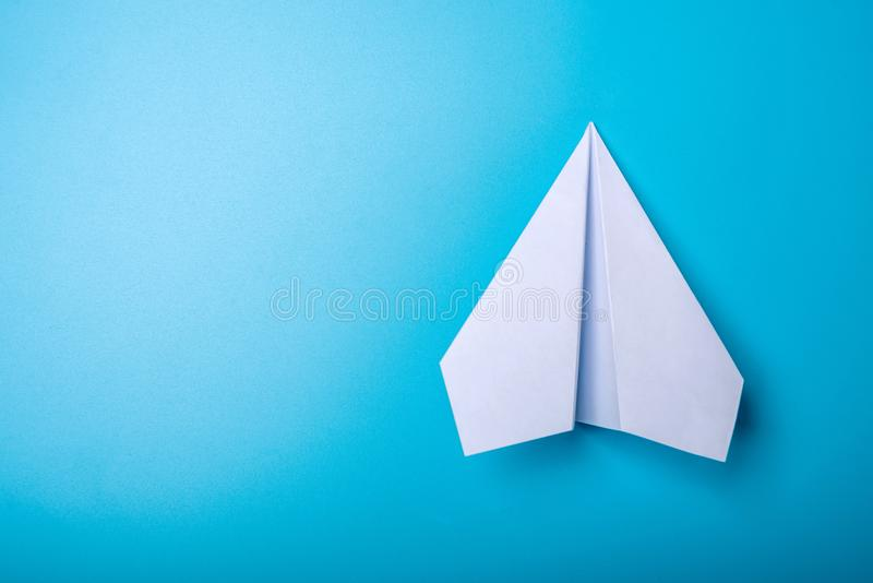 White paper origami airplane lies on pastel blue background. Top view royalty free stock photography