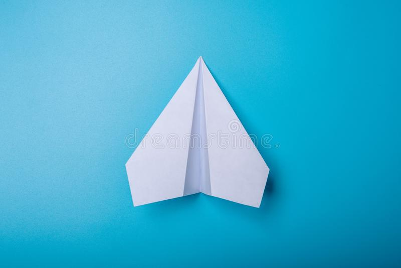 White paper origami airplane lies on pastel blue background. Top view royalty free stock photos