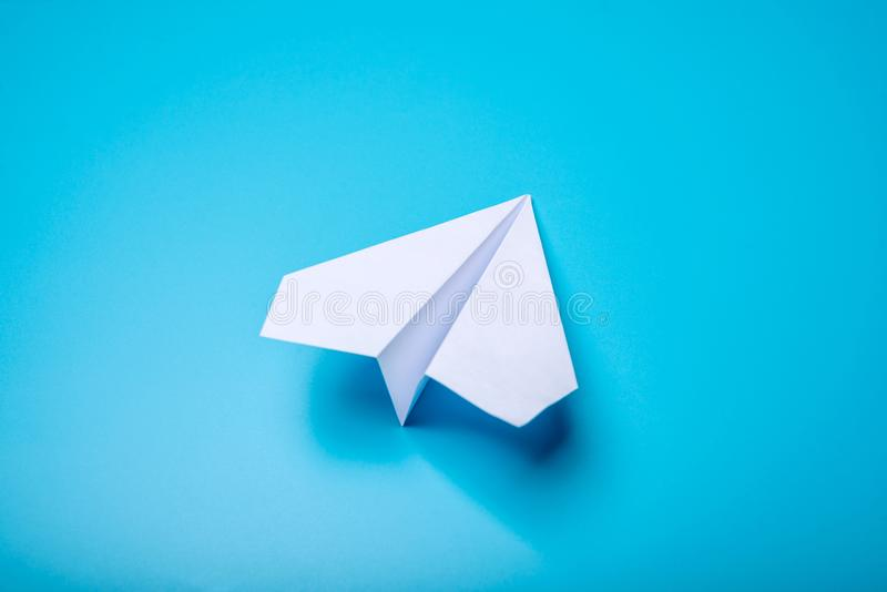 White paper origami airplane lies on pastel blue background. Top view royalty free stock image