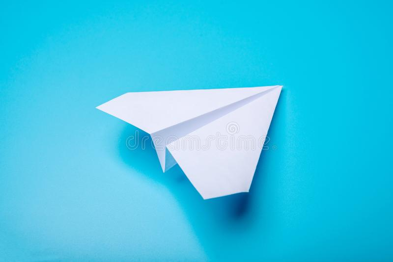 White paper origami airplane lies on pastel blue background. Top view stock photos
