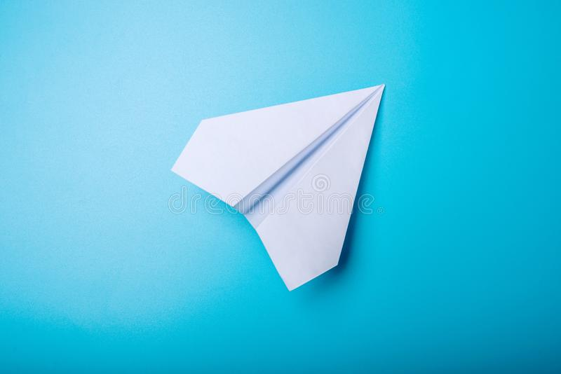 White paper origami airplane lies on pastel blue background. Top view stock image