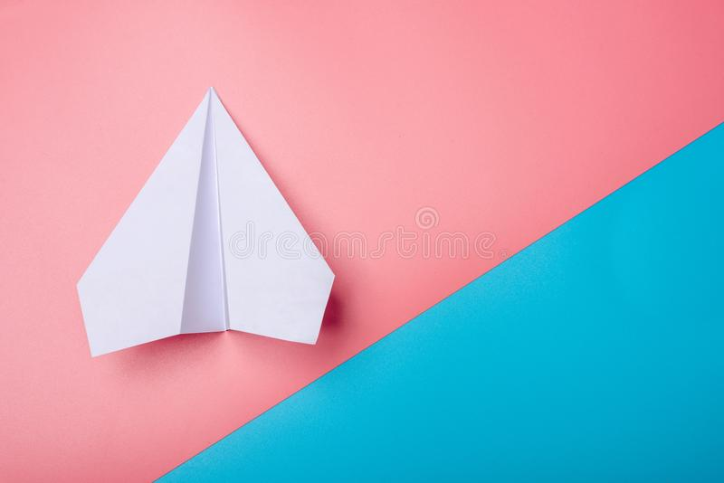 White paper origami airplane lies on pastel colors background. Top view stock image