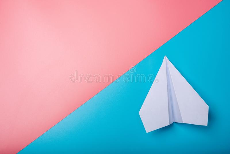 White paper origami airplane lies on pastel colors background. Top view stock images