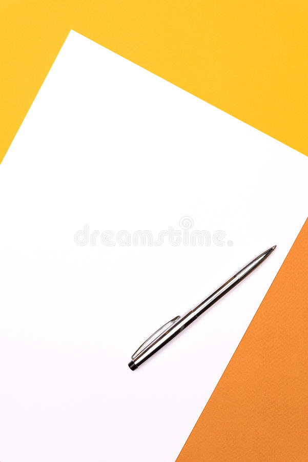 White paper and pen on yellow brown background royalty free stock photography