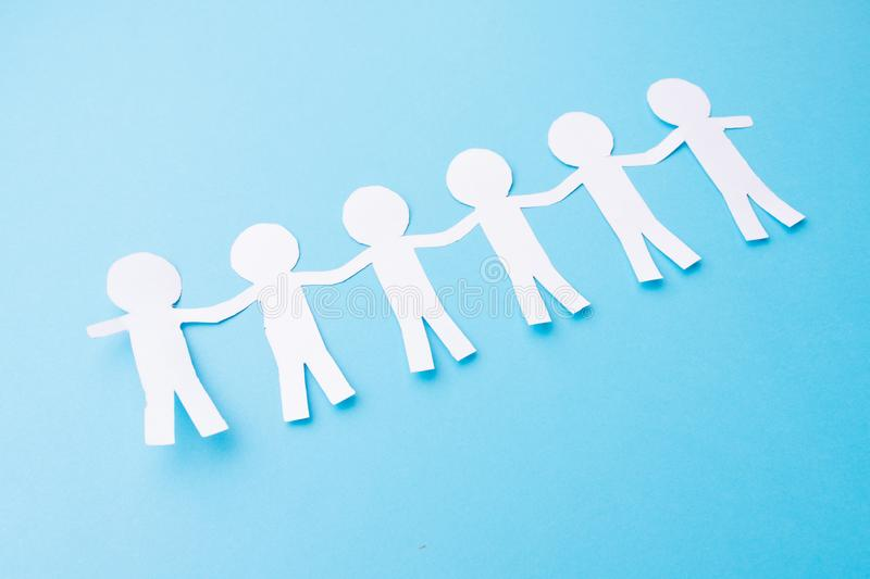 White paper people holding hands. Blue background. Chain, human, teamwork, concept, relationship, together, doll, cutout, friends, join, figure, isolated royalty free stock photo