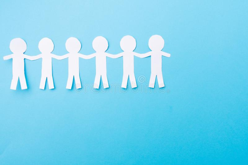 White paper people holding hands. Blue background. Place for text. White paper people holding hands. Blue background, chain, human, teamwork, concept royalty free stock image