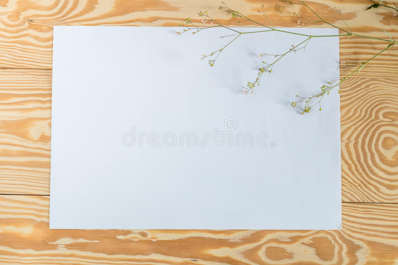 The white paper is placed on a wooden deck with flowers and leaves. stock images