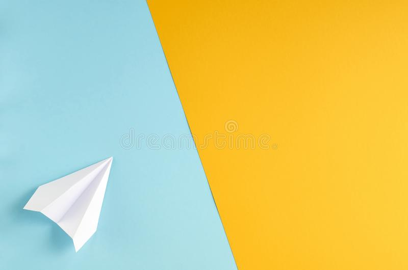 White paper plane on blue and yellow background composition. Flat lay and top view photo, fly, golden, layout, above, bright, card, concept, copy, space royalty free stock images