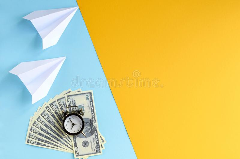 White paper planes, alarm clock and money on blue and yellow background composition. Flat lay and top view photo, cash, time, dollar, 50, fly, watches, golden stock photos