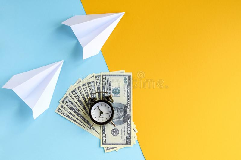 White paper planes, alarm clock and money on blue and yellow background composition. Flat lay and top view photo, cash, time, dollar, 50, fly, watches, golden royalty free stock photos