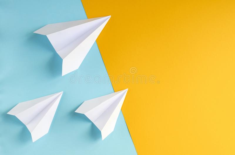 White paper planes on blue and yellow background composition. Flat lay and top view photo, fly, golden, layout, above, bright, card, concept, copy, space stock image