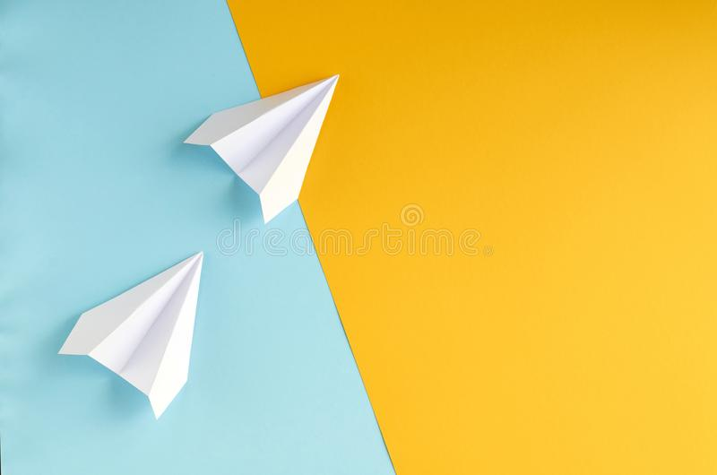 White paper planes on blue and yellow background composition. Flat lay and top view photo, fly, golden, layout, above, bright, card, concept, copy, space royalty free stock photography