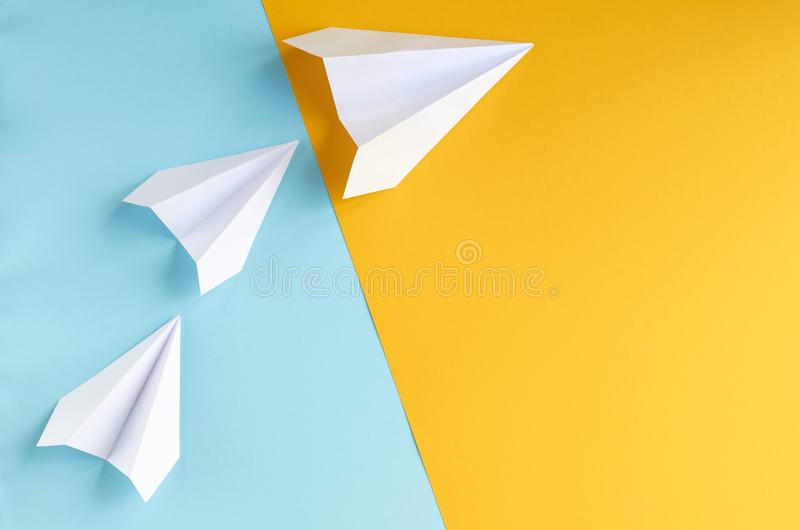 White paper planes on blue and yellow background composition. Flat lay and top view photo, fly, golden, layout, above, bright, card, concept, copy, space royalty free stock photo