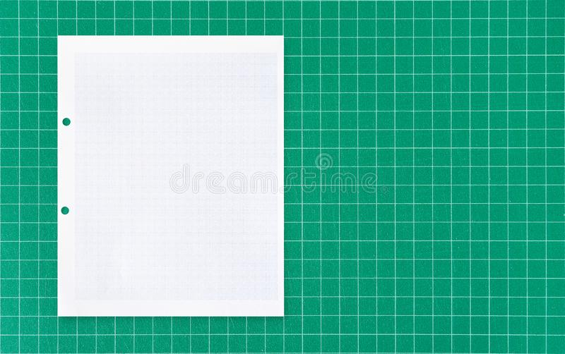 White paper sheet with grid line pattern on green mat background. White paper sheet with grid line pattern on green cutting mat background royalty free stock image
