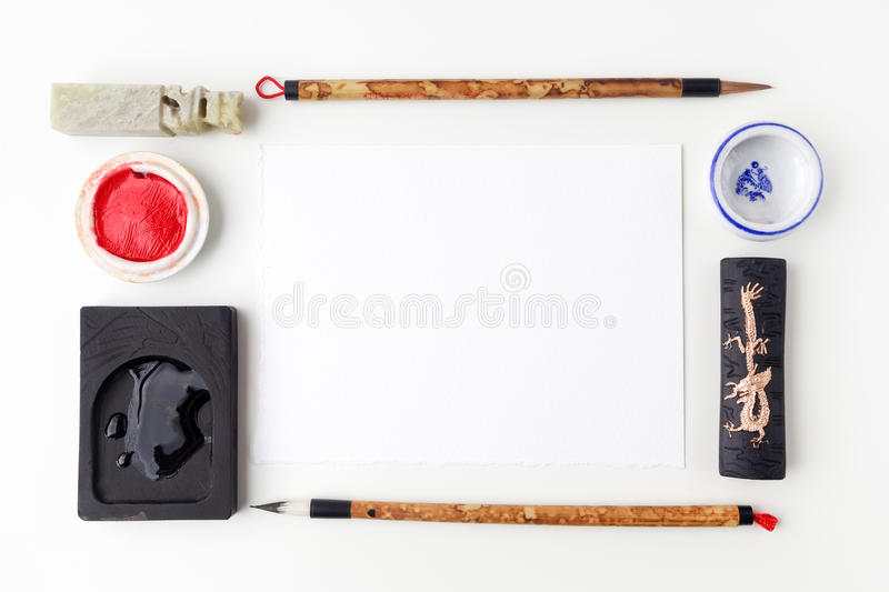 White paper sheet mockup with calligraphy tools flat lay top