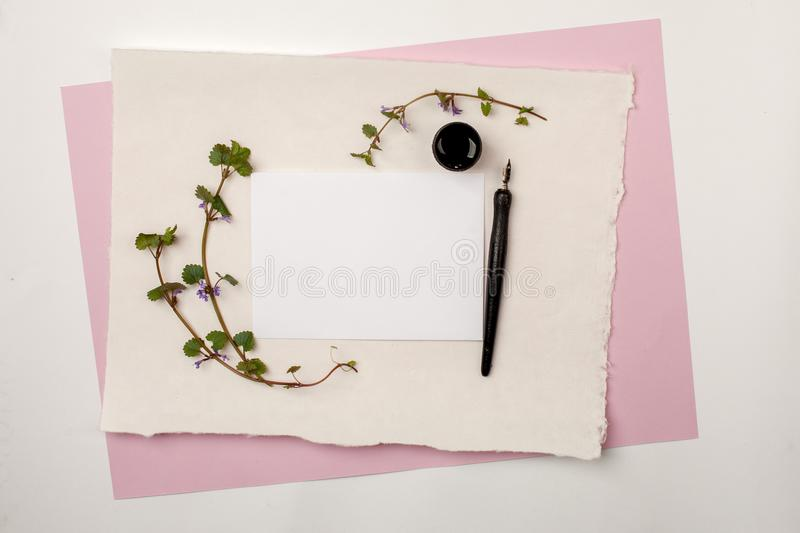 White paper sheet mockup on pink pastel background with calligraphy nib and ink. For invitation, wedding, decoration. White paper sheet mock up on pink pastel royalty free stock photos