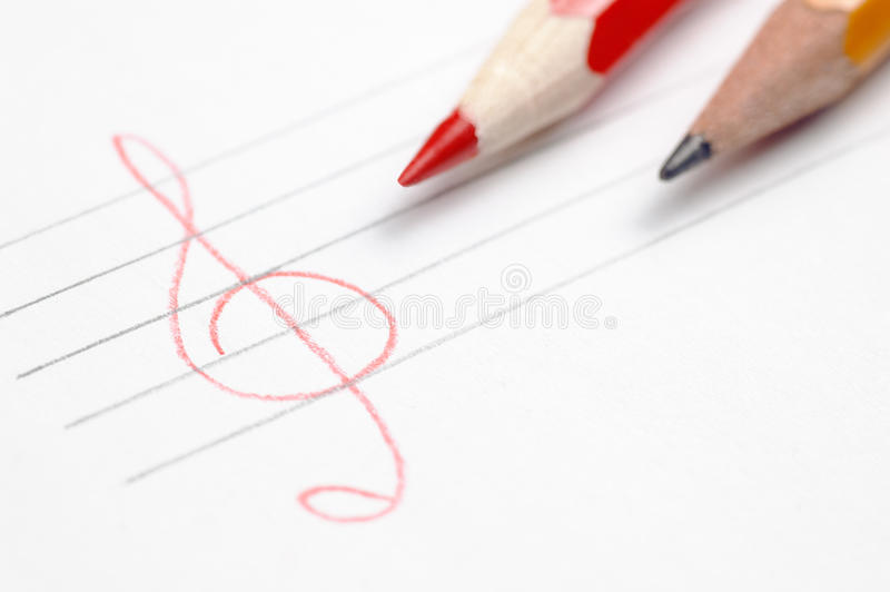 White paper sheet with two pencils and hand drawn. White paper sheet with two different pencils and hand drawn stave and treble clef shallow depth of field have stock images