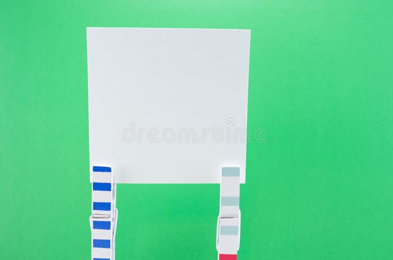 White paper sheets on clothespins on green background, mock up. Copy space royalty free stock photos
