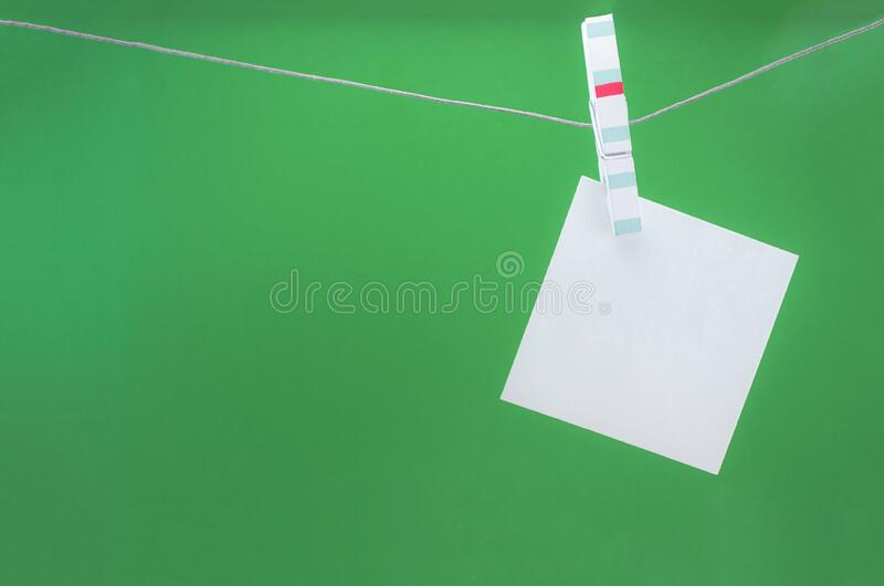 White paper sheets on clothespins on green background, mock up. Copy space stock images