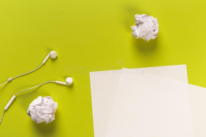 White paper sheets on coloured backgroung with rolled paper and white earphones. White paper sheets on coloured background with rolled paper and white earphones royalty free stock photography