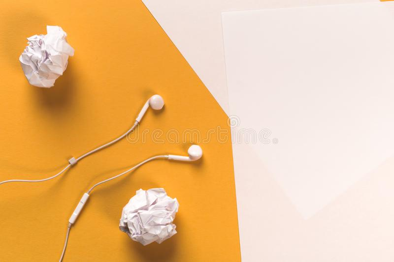 White paper sheets on coloured backgroung with rolled paper and white earphones.  royalty free stock photo