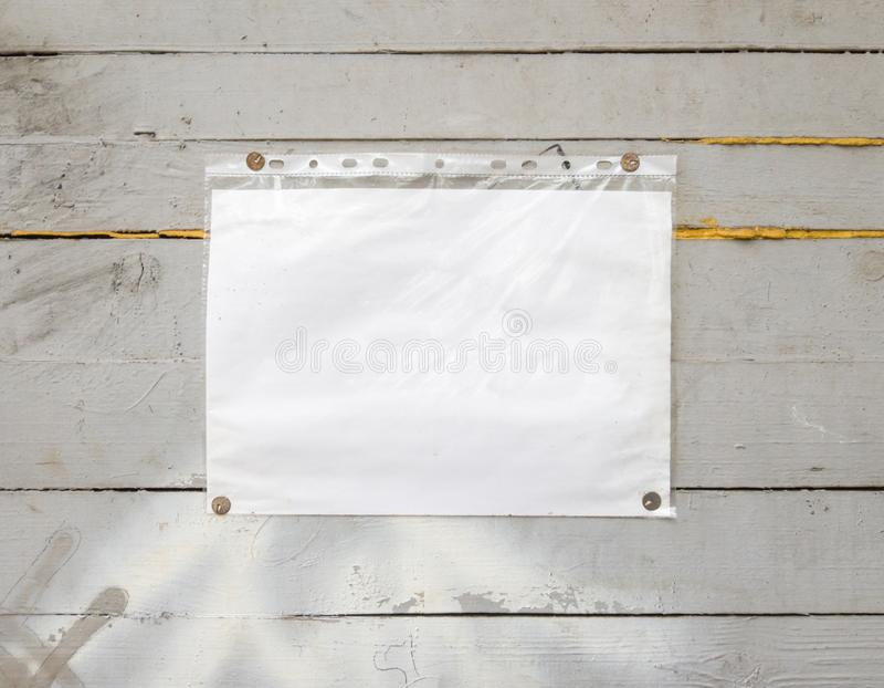 White paper sign with rivets, vintage background on a gray wooden old backdrop. Wooden textured wall, weighs a white blank royalty free stock photography